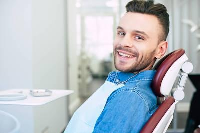 man smiling in a dental chair in parker co